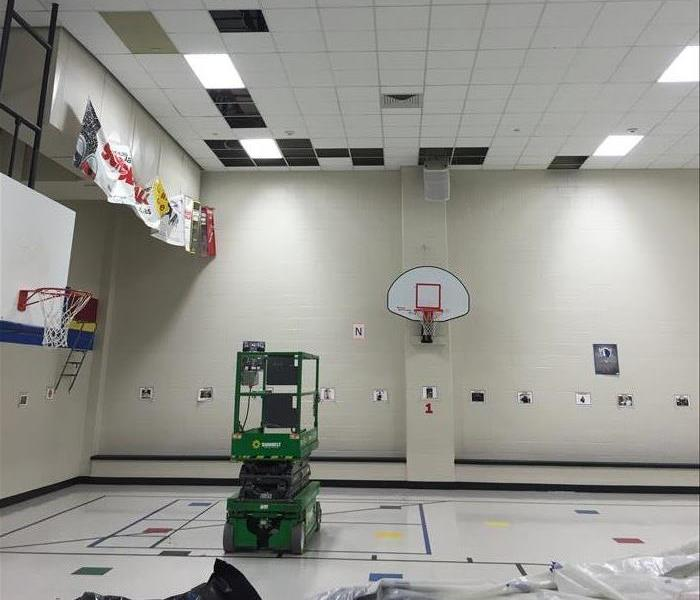 A large school gym being prepped for mitigation work after a flood.