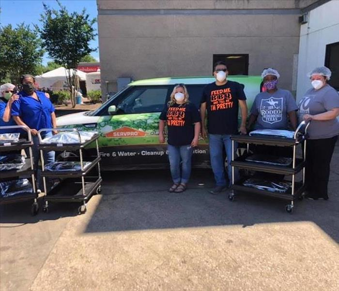 A group of people standing around a SERVPRO vehicle.