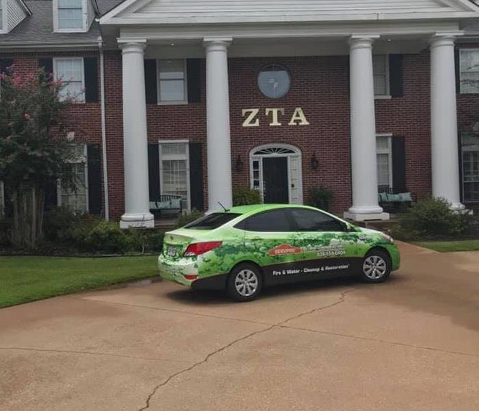 A SERVPRO car in front of a Sorority building.