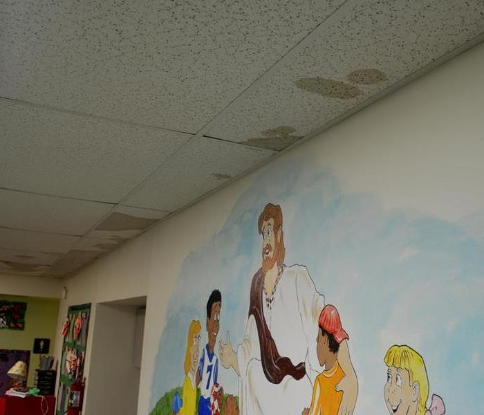 A flooded Sunday school room with water damage to the ceiling.
