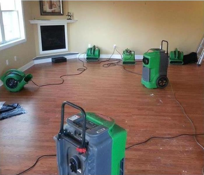A SERVPRO fan in the living room of a home that has been flooded and is now drying.