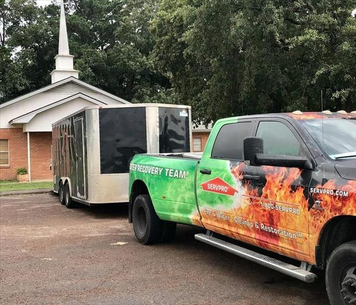 A SERVPRO truck in front of a small church