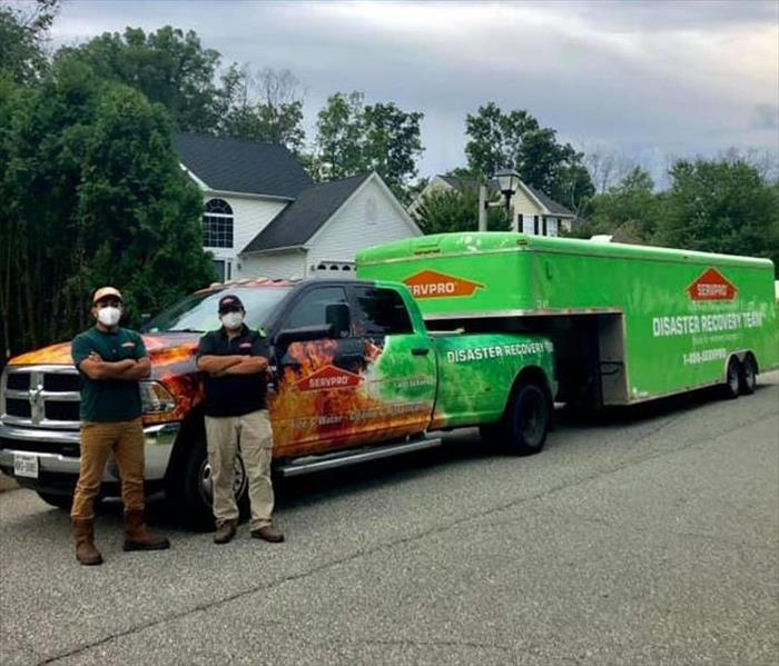 SERVPRO Employees standing in front of a SERVPRO Vehicle.
