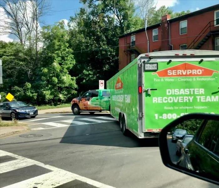 A SERVPRO truck pulling a trailer on a busy street.