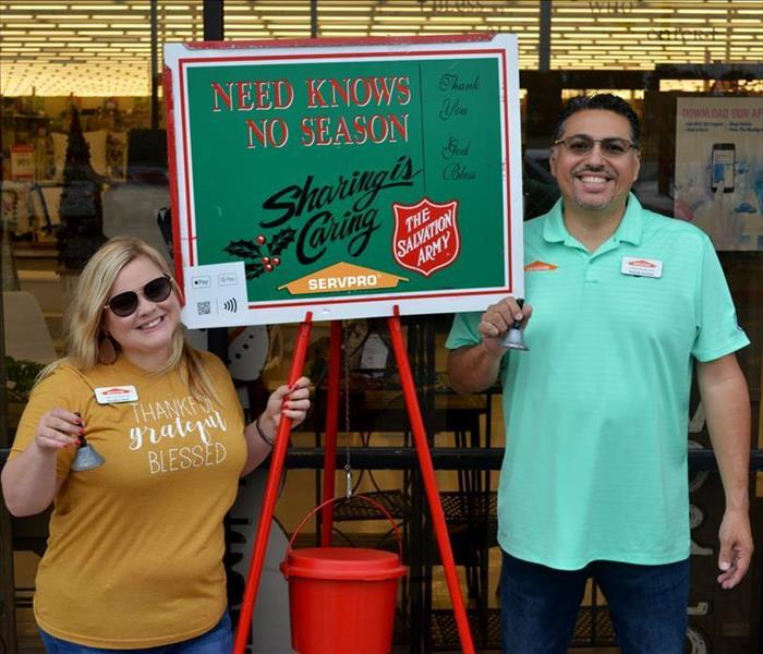 Two people ringing a bell for the salvation army.