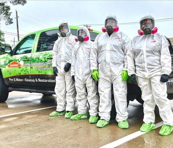 SERVPRO employees wearing TYVEK suits in front of a SERVPRO vehicle.