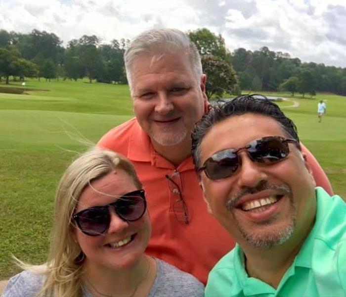 3 People posing for a picture on a golf course.