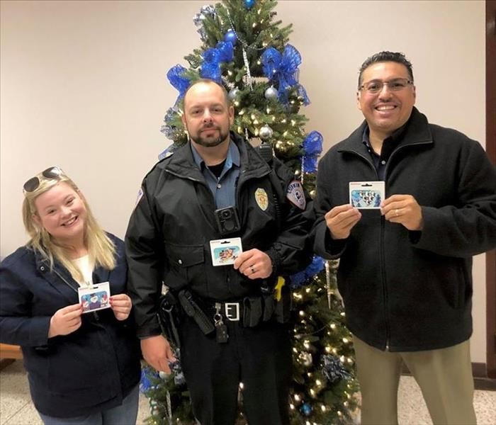 Two people posing with a cop while holding gift cards.
