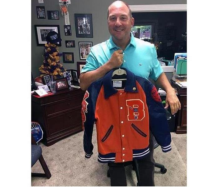 A man holds a freshly restored letterman jacket.