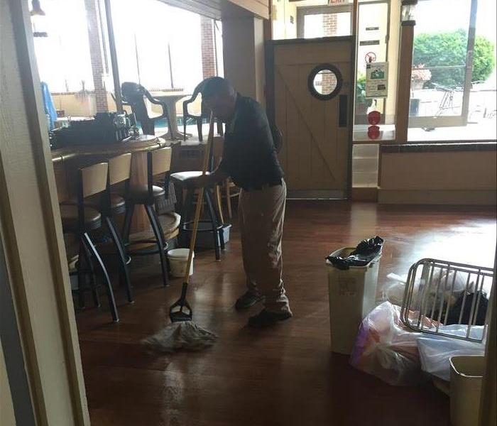 A SERVPRO employee drying flooring after a water loss.