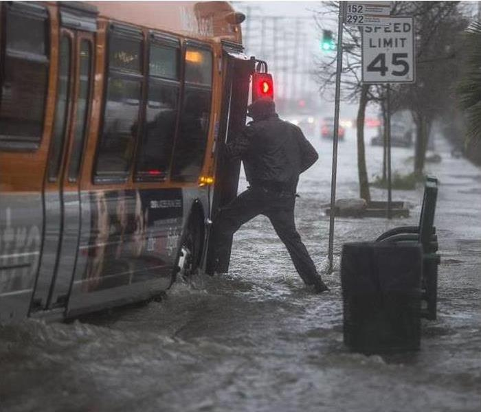 A man boards a bus in heavy rain with rising water.