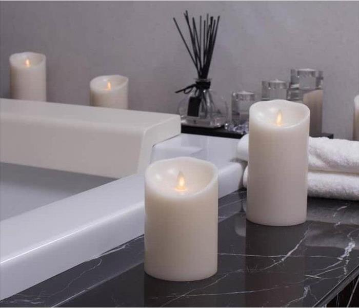 Flameless candles sitting on a ledge of a tub.